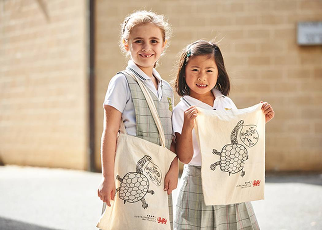 Kiara and Allegra from Penrhos College with the reusable shopping bags they made to raise money for Perth Zoo's turtle breeding program.